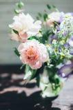 Buketten av den vita pioner, kamomillar och irins blommar i den glass vasen Blåtthav, Sky & moln Tonat foto Royaltyfria Foton