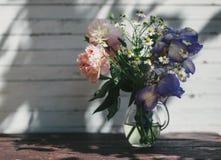Buketten av den vita pioner, kamomillar och irins blommar i den glass vasen Blåtthav, Sky & moln Tonat foto Royaltyfria Bilder