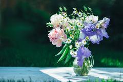 Buketten av den vita pioner, kamomillar och irins blommar i den glass vasen Blåtthav, Sky & moln Tonat foto Royaltyfri Bild
