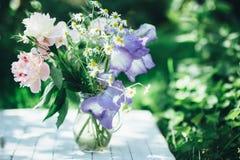 Buketten av den vita pioner, kamomillar och irins blommar i den glass vasen Blåtthav, Sky & moln Tonat foto Arkivfoton