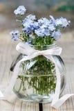 Buketten av förgätmigejen blommar i den glass vasen Arkivbilder