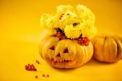 buketten av guling blommar i pumpa halloween Arkivfoto