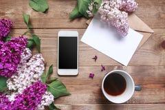 Buketten av lilan blommar på träplankor med det tomma kortet för text, gåva, kaffe och mobiltelefon Top beskådar Royaltyfria Bilder