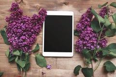 Buketten av lilan blommar på träplankor med minnestavlan Royaltyfri Foto