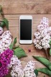 Buketten av lilan blommar på träplankor med mobiltelefonen Royaltyfria Bilder