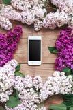 Buketten av lilan blommar på träplankor med mobiltelefonen Arkivfoto