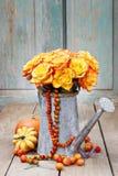 Buketten av orange rosor i silver som bevattnar kan Royaltyfri Bild