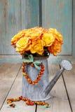 Buketten av orange rosor i silver som bevattnar kan Arkivbilder