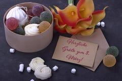 Buketten av röda gula callas med marshmallowmarmelad i en trärund ask och kuvertet på grå färger hårdnar bakgrund och bokstaven Arkivfoto