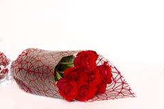 Buketten av röda rosor ligger på en vit bakgrund arkivbilder