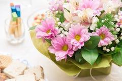 Buketten av rosa färger blommar på en tabell med fester Fotografering för Bildbyråer