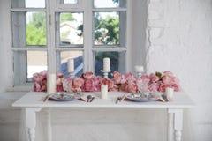 Buketten av rosa orkid?r, rosor och peons dekorerar den ?ta middag tabellen n?ra f?nstret arkivbilder