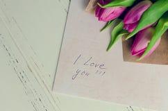 Buketten av rosa tulpan med anmärkningar ÄLSKAR JAG DIG Arkivbild