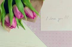 Buketten av rosa tulpan med anmärkningar ÄLSKAR JAG DIG Arkivfoto