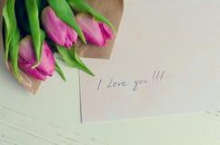 Buketten av rosa tulpan med anmärkningar ÄLSKAR JAG DIG Royaltyfri Fotografi