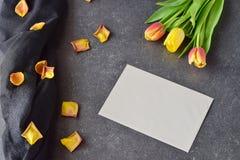 Buketten av rosiga och gula tulpan på svärtar abstrakt bakgrund, med torra kronblad Utrymme för text Romanskt begrepp Royaltyfri Fotografi