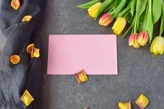 Buketten av rosiga och gula tulpan på svärtar abstrakt bakgrund, med torra kronblad Utrymme för text Romanskt begrepp Arkivbilder