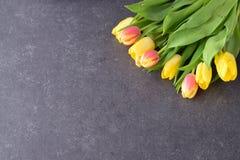Buketten av rosiga och gula tulpan på svärtar abstrakt bakgrund Utrymme för text Romanskt begrepp Fotografering för Bildbyråer