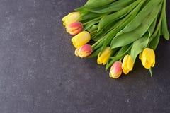Buketten av rosiga och gula tulpan på svärtar abstrakt bakgrund Utrymme för text Romanskt begrepp Arkivbilder