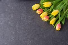 Buketten av rosiga och gula tulpan på svärtar abstrakt bakgrund Utrymme för text Romanskt begrepp Arkivfoto