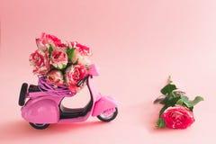 Buketten av rosor blommar i korg på backseaten av den gulliga rosa sparkcykeln och den stora rosen på rosa bakgrund royaltyfri bild