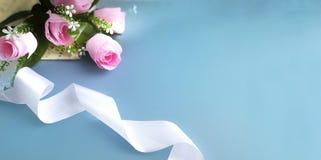 Buketten av rosor, rullade bandet på blå bakgrund royaltyfria bilder