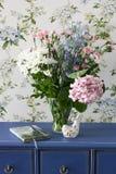 Buketten av sommar blommar i stilen av Provence på den blåa skänken Arkivbild