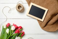Buketten av tulpanblommor, tom bildram, tvinnar, säckväv på den vita trätabellen Tappninghälsningkort för kvinnas dag, mödrar royaltyfri bild