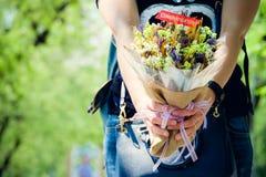 Buketten blommar lyckönskan i händerna Fotografering för Bildbyråer