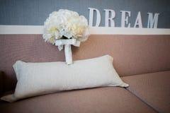 Buketten för brud` s på en soffa Dröm- text i bakgrunden royaltyfri foto