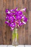 Bukettorkidén blommar i den tropiska gården på en trätabell Royaltyfri Foto
