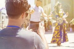BUKHARA, USBEKISTAN - 25. MAI 2018: Seide und Gewürz-Festival 2018 Junger Mann, der selfie mit bukharian Musikern und Tänzern nim lizenzfreie stockbilder
