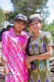 BUKHARA, UZBEKISTÁN - 11 DE MAYO DE 2011: Dos mujeres jovenes del Uzbek vistieron tradicionalmente la presentación dentro del mau Fotografía de archivo