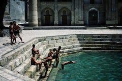 Bukhara/Uzbekistán - 5 de mayo de 2010: muchachos que juegan cerca de los pozos y de las reservas de agua antiguos en la ciudad e fotografía de archivo