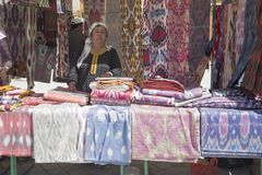 BUKHARA, UZBEKISTÁN - 25 DE MAYO DE 2018: Seda y festival 2018 de las especias Mujer de las ventas que vende la tela de seda asiá imagen de archivo libre de regalías