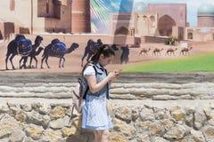BUKHARA UZBEKISTAN, MAJ, - 25, 2018: Jedwab i pikantność festiwal 2018 Szkolna dziewczyna z telefonu komórkowego odprowadzeniem p Zdjęcia Royalty Free