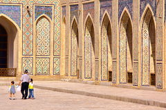 BUKHARA, UZBEKISTAN - MAY 9, 2011: An Uzbek man with his two children walking in the courtyard of the Poy Kalon mosque. An Uzbek man with his two children stock photos
