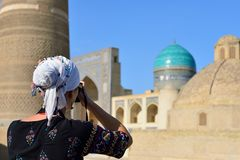 Bukhara, Uzbekistan, Silk Route. Bukhara, Uzbekistan, Tourist on the main square admiring ancient monuments of Bukhara of architectural pearl on the Silk Route stock photography