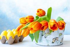 Bukiet świeży żółty tulipan w wazowych i dekoracyjnych jajkach na nieba błękita tle zdjęcia royalty free