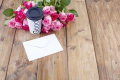 Bukiet świeże różowe róże na drewnianym stole Wiadomość jest w białej kopercie Bezpłatna przestrzeń dla teksta lub pocztówek obraz royalty free