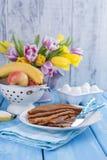 Bukiet świezi tulipany kolor żółty, menchie, kwiaty i bliny niebieska tła Wiosna owoc wazowe Bezpłatna przestrzeń dla zdjęcia royalty free