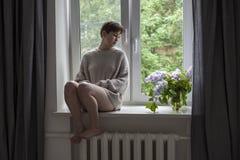 Bukiet bez kapuje w przejrzystym słoju na białym krześle jako dekoracja wnętrze Dziewczyna siedzi na okno obraz stock