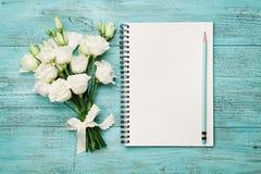 Bukiet biali kwiaty i opróżnia papierowego prześcieradło na turkusowym wieśniaka stole od above Piękna rocznik karta, odgórny wid Zdjęcie Royalty Free
