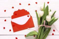 Bukiet biali tulipany i czerwona koperta na białym drewnianym backg zdjęcie royalty free