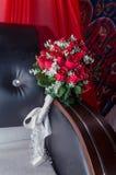 Bukiet czerwone róże na brown kanapie na szkarłatnym tle z Arabskimi ornamentami Obrazy Stock