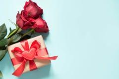 Bukiet czerwone róże, prezent z czerwonym faborkiem i serce na błękicie s karciany valentine z bliska kosmos kopii Obrazy Royalty Free