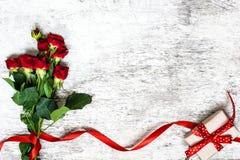 Bukiet czerwone róże z czerwonym faborku i prezenta pudełkiem Fotografia Royalty Free