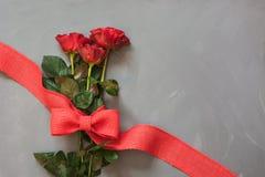 Bukiet czerwone róże i czerwony faborek na popielatym tle s karciany valentine z bliska kosmos kopii Zdjęcia Stock
