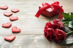 Bukiet czerwone róże, prezent z czerwonym faborkiem i serce na drewnianej desce s karciany valentine kosmos kopii Obraz Stock