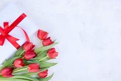 Bukiet czerwoni tulipany i pude?ko z ??kiem na bia?ym tle Niespodzianka i kwiaty dla romantycznego wakacje Prezent dla mamy lub obraz stock